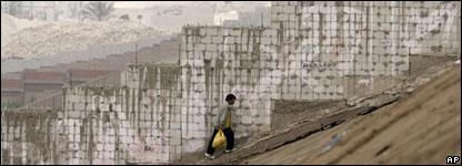 Hombre peruano sube una cuesta en un barrio pobre de Lima
