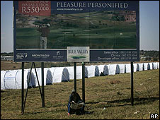 A man reads a newspaper under an advertising billboard in front of tents set by the United Nations to house victims of anti foreign violence in Midrand, South Africa, Sunday June 1, 2008.