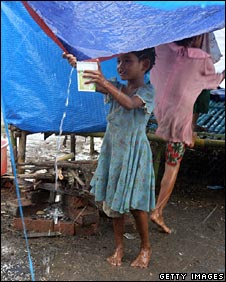 Child collecting water from her tent in Labutta