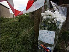 Flowers laid close to the path that leads to where a 17-year-old boy died after being trapped in flood water