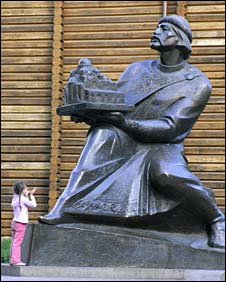 Girl peering up at statue of Yaroslav the Wise