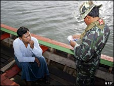 A Thai soldier checks identification documents of a Burmese worker in Ranong province in April 2008