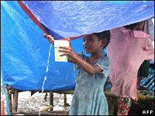 A child collects rain water running off a tent at a displaced people camp in Labutta on 31 May 2008