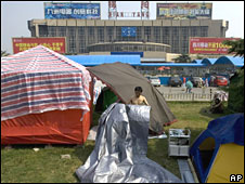 A Mianyang resident folds a tarpaulin for his tent in front of the Mianyang Train Station on 5 June 2008. The clock is stopped at 1428, the time the May 12 earthquake struck