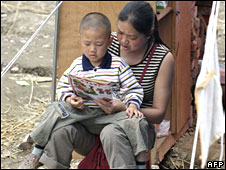 Earthquake survivor reads with her child outside a tent on 31 May 2008