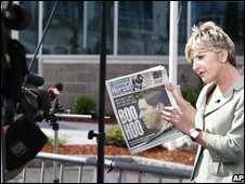 A television reporter holding a Boston Herald newspaper
