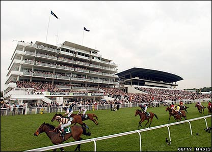 The horses pass the grandstand at Epsom
