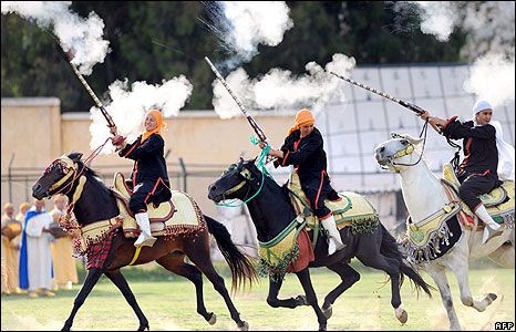 Women horse riders fire in the sky using old gunpowder guns during a traditional fantasia parade as part of the 1200th anniversary of the creation of the city of Fez on May 31