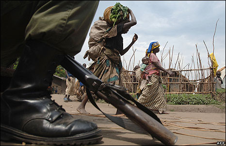 Displaced people pass by a government soldier on June 5, 2008 in Kinyandonyi, 85km north of the provincial capital Goma. Nine people have reportedly been killed when FDLR (Democratic Force for the Lib