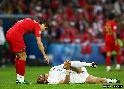 Servet Cetin of Turkey lies on the ground after being challenged by Cristiano Ronaldo
