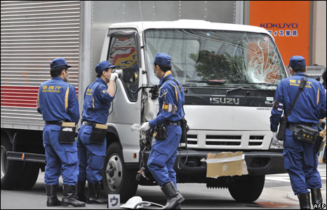 Policemen inspect a truck believed to be the one used by the suspect