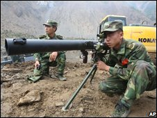 An engineering soldier prepares to fire a missile to blast boulders in a man-made sluice channel in Tangjiashan lake