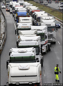 A policeman tries to keep a lane open as lorries move in to block the M-40 ring road in Madrid, 9 June 2008