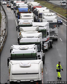 A policeman tries to keep a lane open as lorries move in to block the M-40 ring road in the Spanish capital, Madrid, 9 June 2008