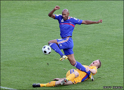 Nicolas Anelka of France is tackled by Romania's Dorin Goian