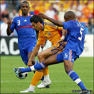 Daniel Niculae of Romania is challenged by Eric Abidal and William Gallas
