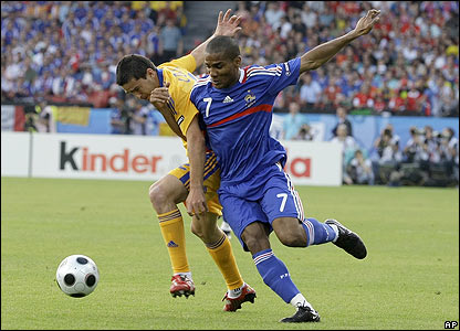 Frances Florent Malouda grapples with Romania's Cosmin Contra