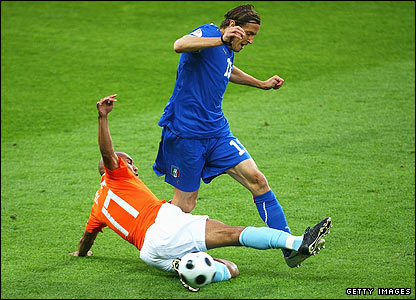 Italy's Massimo Ambrosini is tackled by Nigel de Jong
