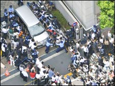 A crowd of photographers surrounds Tomohiro Kato, suspected of Sunday's stabbing spree in Tokyo, as he is transferred by police on Tuesday