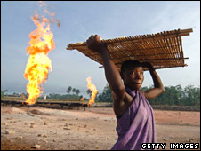 Woman carrying tapioca seeds next to a gas flare fire in Niger Delta