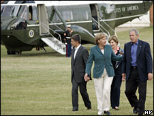 George W Bush, right, is welcomed by German Chancellor Angela Merkel, second from left, upon his arrival at a government guest house in Meseberg north of Berlin, Germany, 10 June 2008