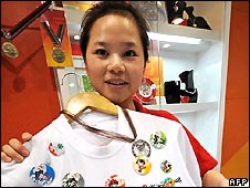 A Chinese salesgirl shows Olympic badges and souvenirs on sale at an official outlet in Beijing