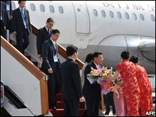 Taiwan's Chiang Pin-kung is presented with a bouquet of flowers on arrival in Beijing on June 11, 2008.