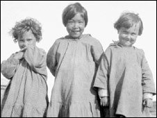 Two Metis children standing either side of an Inuit child from the All Saints residential school in Shingle Point, Yukon, 1930. JF Moran/Library and Archives Canada/PA-102086