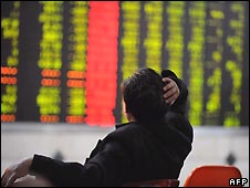 Chinese investor stares at stock market board