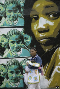 Mujer con bebé pasa frente a un mural que refleja a la población negra, en Río de Janeiro