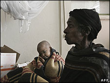 A malnourished boy sits with his mother in a feeding center on June 8, 2008 in Shanto, Ethiopia.
