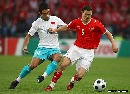 Stephan Lichtsteiner of Switzerland controls the ball in front of Arda Turan