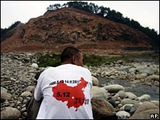 A man wearing a T-shirt showing the date and time of the quake sits on a hillside in Luoshui on 8 June 2008