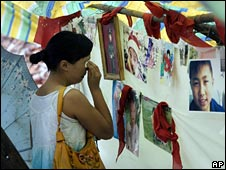 A woman looks at pictures of children killed when a school collapsed in Luoshui, 8 June 2008