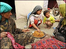 Displaced Afghans eat in camp, Kabul