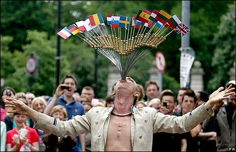 Street performer The Space Cowboy attempts to swallow 27 swords decorated with the flags of the EU states on 11 June in Dublin