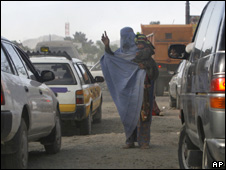 An Afghan woman holds her baby as she begs money at a traffic jam in Kabul, Afghanistan (file photo)