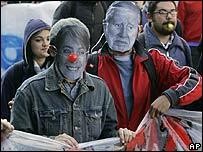 Manifestantes portan máscaras de la presidenta Michelle Bachelet y del general Pinochet