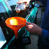 Man using funnel to fill car