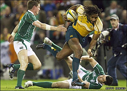 Lote Tuqiri bowls over an Ireland player as Ronan O'Gara (left) tries to get to grips with the Wallaby winger