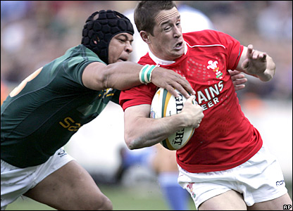 Wales winger Shane Williams is tackled by Adrian Jacobs