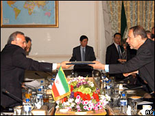 Iranian Foreign Minister Manouchehr Mottaki, left, receives a package of incentives from EU foreign policy chief Javier Solana in Tehran on 14 June 2008