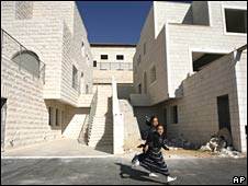 Jewish girls run past a building under construction in Ramat Shlomo on 13 June 2008