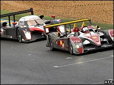 Rinaldo Capello's Audi leads Jacques Villeneuve's Peugeot on a wet track during the Le Mans 24 Hours