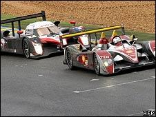 Rinaldo Capello's Audi leads Jacques Villeneuve's Peugeot on a wet track during the Le Mans 24 Hours