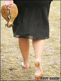 A woman walks barefoot at Royal Ascot