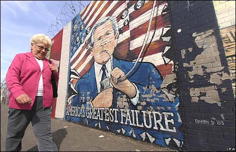A woman walking past a Falls Road mural featuring George Bush