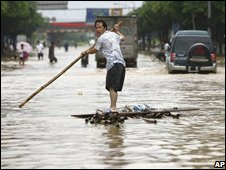 A resident paddles on a home-made raft on a flooded street at Xiaojiejiao Village at Humen Township in Dongguan, 13 June