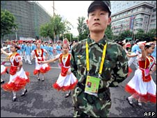 A soldier keeps watch as Uighur Muslim students dance in celebration of the Olympic torch in Urumqi, Xinjiang, on Tuesday