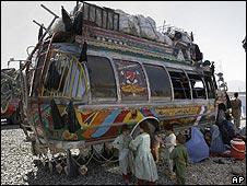 Afghan returnees by a bus in Kabul